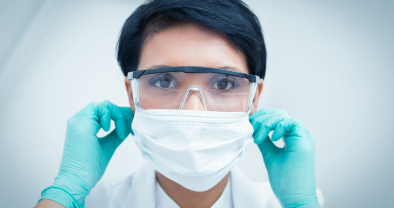 Dental hygienist wearing a mask, eye protection, and gloves