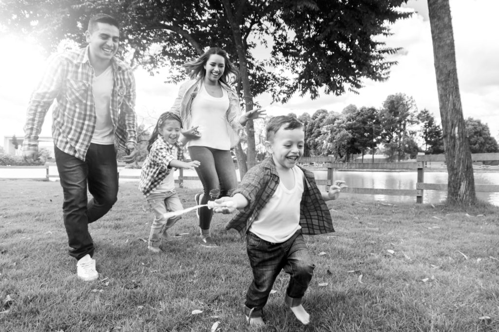 Family of four running and playing in the park
