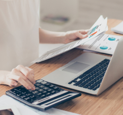 Practice Analysis –Take Back Your Power. A woman sits at her desk in a brightly lit office analyzing a stack of practice view papers while she confirms numbers with her calculator and consults her laptop.