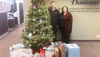 Two Burkhart Associates stand near a tree with gifts ready to go to the The Good Neighbor Center