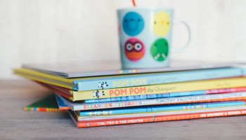 A stack of kids books and a mug