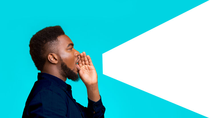 A black man with a slight beard and close-cropped hair, wearing a dark colored shirt, stands in profile with his hand cupped around his mouth as if he's shouting to the world. The background is a bright solid teal and there is a white graphic shape to the right of the man mimicking a megaphone. The megaphone starts at the man's mouth and vibrantly, loudly shoots off the page.