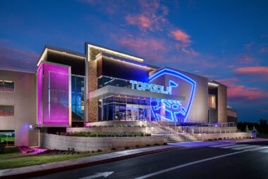 An exterior photo taken of a TopGolf venue at dusk. The blue and purple neon lights highlight the modern architecture of the building. The angles and lights add a lot of energy to the building, capturing the essence of the space.