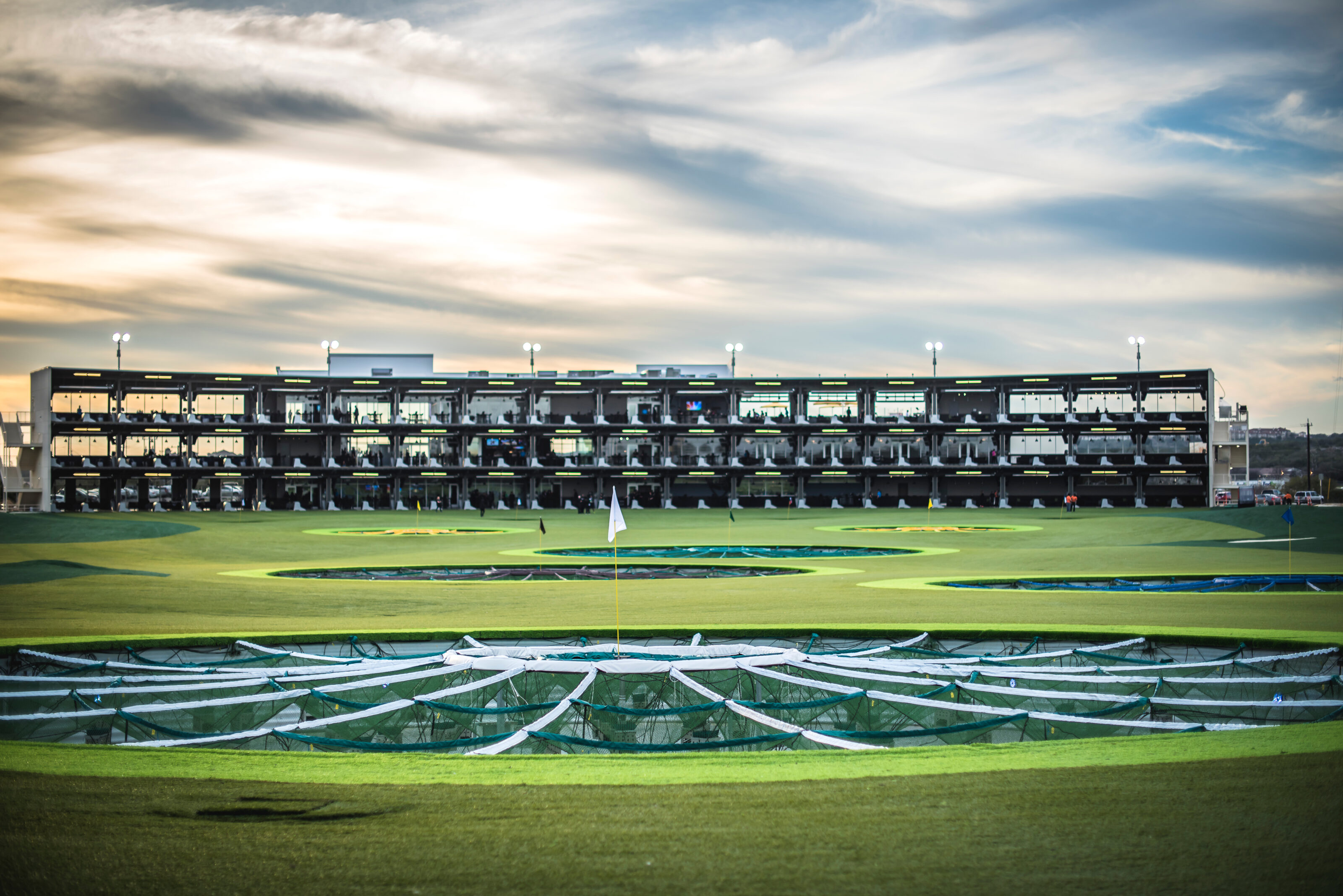 """TopGolf from the """"outfield."""" Toward the back of the photo are the bays where participants can take aim at the giant outfield targets. The outfield targets are comprised of several large openings in the bright green grass of the outfield."""