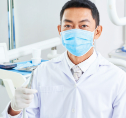 A dentist stands in a bright, light dental operatory holding a handpiece. In the very light colored background, the dentist, wearing a blue mask, carries the focal point of the image.