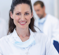 A woman doctor with dark hair smiles at the camera. She is wearing a white lab coat and has a mask around her neck. Behind her, out of focus, we can see three additional people wearing similar clothing referencing paperwork in front of them. They are in a bright white room.