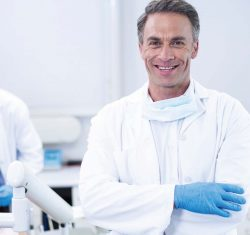 Male dentist smiles broadly at the camera. Around his neck he's wearing a mask, dressed in a white doctor's coat with blue gloves, he stands in the foreground of the image. Out of focus in the background a team member addresses the needs of a patient reclined in a dental chair. The whole space is bright and light.