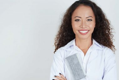 A black female dentist, wearing a white doctor's coat, smiles big facing the camera. Hanging around her neck is a grey mask.