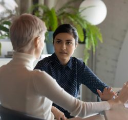 Delivering feedback to employees can be an intense situation. There are two women in this image –an Indian woman with a serious expression on her face is facing the camera, we see the back view of a caucasian business woman participating in the conversation. Both women are making hand gestures that seem to indicate the seriousness of the conversation.