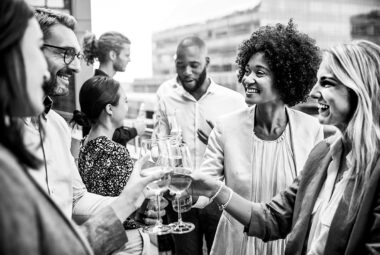 Group of business people and friends gathered for a dental roadshow happy hour event. Four people with different ethnic backgrounds are clinking white wine glasses.